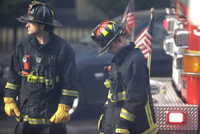 A firefighter, right, lowers his head at the scene of the fatal fire at a four-story brownstone in the Back Bay neighborhood near the Charles River, Wednesday, March 26, 2014, in Boston.
