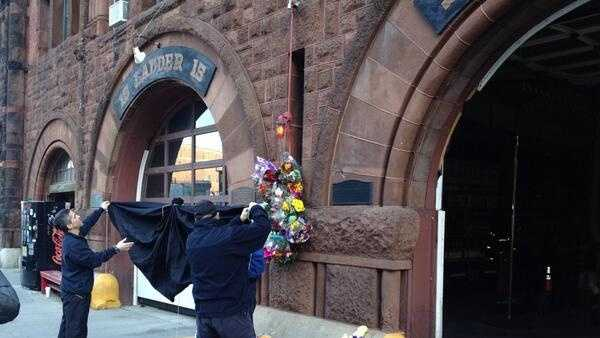 Black bunting is raised at Engine 33 on Boylston Street.
