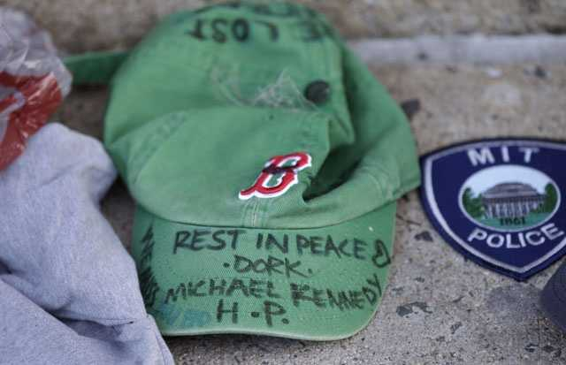 A baseball cap with a written tribute to fallen Boston firefighter Michael Kennedy rests at a makeshift memorial in front of fire station Engine 33, Thursday, March 27, 2014, in Boston. Fire station Engine 33 was the station of fallen firefighters Kennedy and Lt. Edward Walsh and who lost their lives fighting a 9-alarm fire in a four-story brownstone in Boston's Back Bay neighborhood.