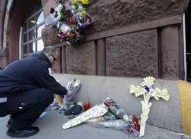 Emergency medical technician David Stewart places flowers at a makeshift memorial on the front of fire station Engine 33/Ladder 15, Thursday, March 27, 2014, in Boston. Engine 33/Ladder 15 was the station of fallen firefighters Lt. Edward Walsh and Michael Kennedy, who lost their lives fighting a nine-alarm blaze in a four-story brownstone in Boston's Back Bay neighborhood.