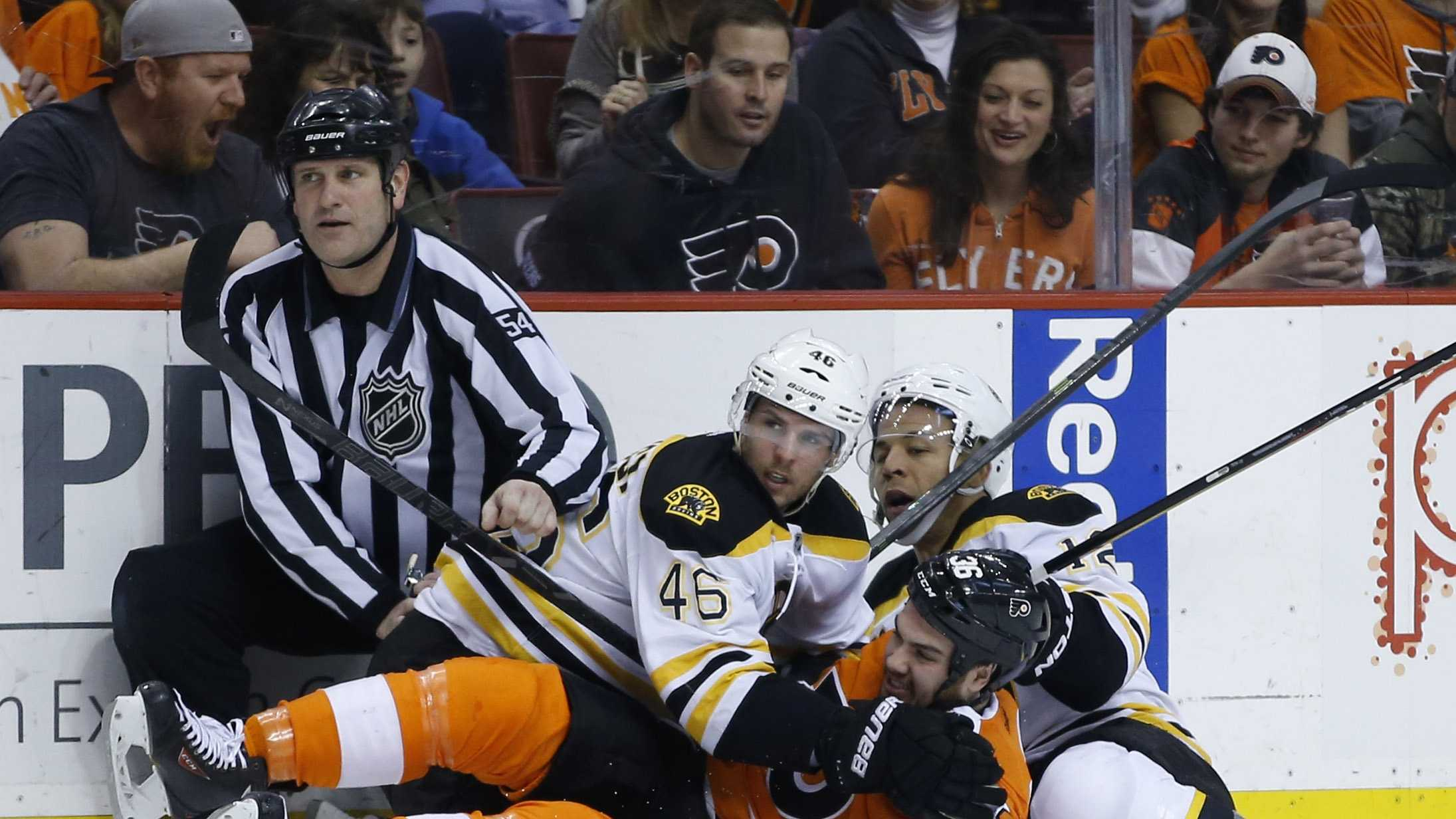 Boston Bruins' Jarome Iginla (12) and David Krejci, of the Czech Republic, collide with Philadelphia Flyers' Zac Rinaldo (36) and linesman Greg Devorski (54) during the first period of an NHL hockey game on Sunday, March 30, 2014, in Philadelphia. (AP Photo/Matt Slocum)