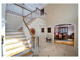 Elegant marble two story foyer opens to family room.