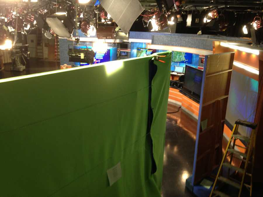 The green screen wall hides the work taking place behind the anchor desk.