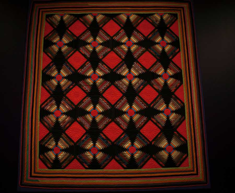 The quilt consists of a number of square blocks. Each block features a small square of fabric in its center&#x3B; around it, the quilt maker sews rectangular strips of different fabrics.