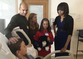 Aaron Hern, 11, of Martinez, Calif. , was wounded by shrapnel while waiting for his mom to finish the race. He is pictured with parents Alan and Katherine, sister Abby and first lady Michelle Obama at Massachusetts General Hospital in Boston a few days after the bombings.