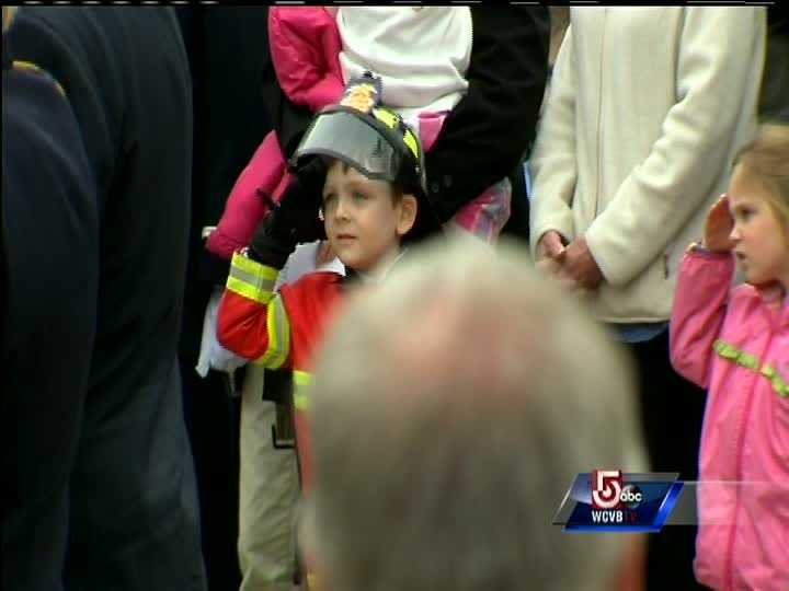 A young boy wears a fire chief outfit.
