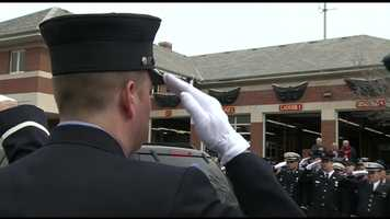 Firefighters standing outside the Watertown Fire House salute the casket with the body of Lt. Ed Walsh as it passes.