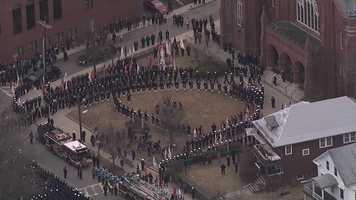 Hundreds of firefighters wait outside St. Patrick's Church in Watertown as the body of Lt. Ed Walsh leaves.