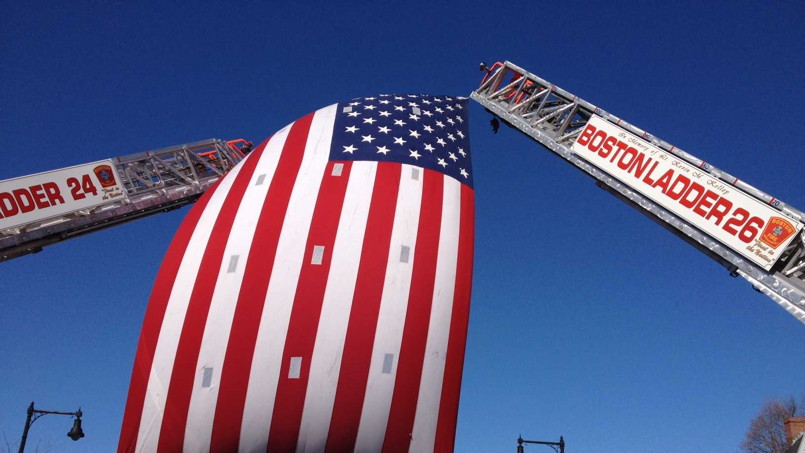 The flag on two Boston ladder trucks across Centre Street.