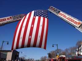 The flag on two Boston ladder trucks across Centre Street.