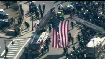 An American flag is raised across Centre Street in West Roxbury.