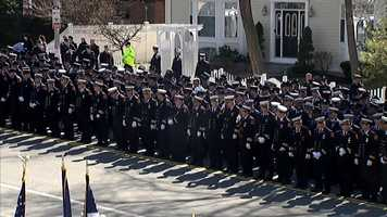 Firefighters stand outsideHoly Name Church in West Roxbury as the body of Michael Kennedy arrives.