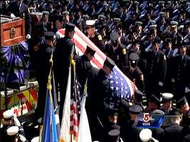 Firefighters place the casket with the body of Michael Kennedy onto Engine 33.