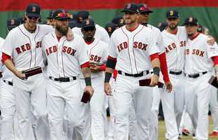 Boston Red Sox players walk on the field after receiving their World Series rings.