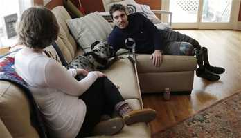 In this March 14, 2014 photo, Jeff Bauman, who lost both his legs above the knee in the Boston Marathon bombing, relaxes on the couch with his fiancee Erin Hurley and dog Bandit, at their Carlisle, Mass., home. The couple are expecting their first child in July.