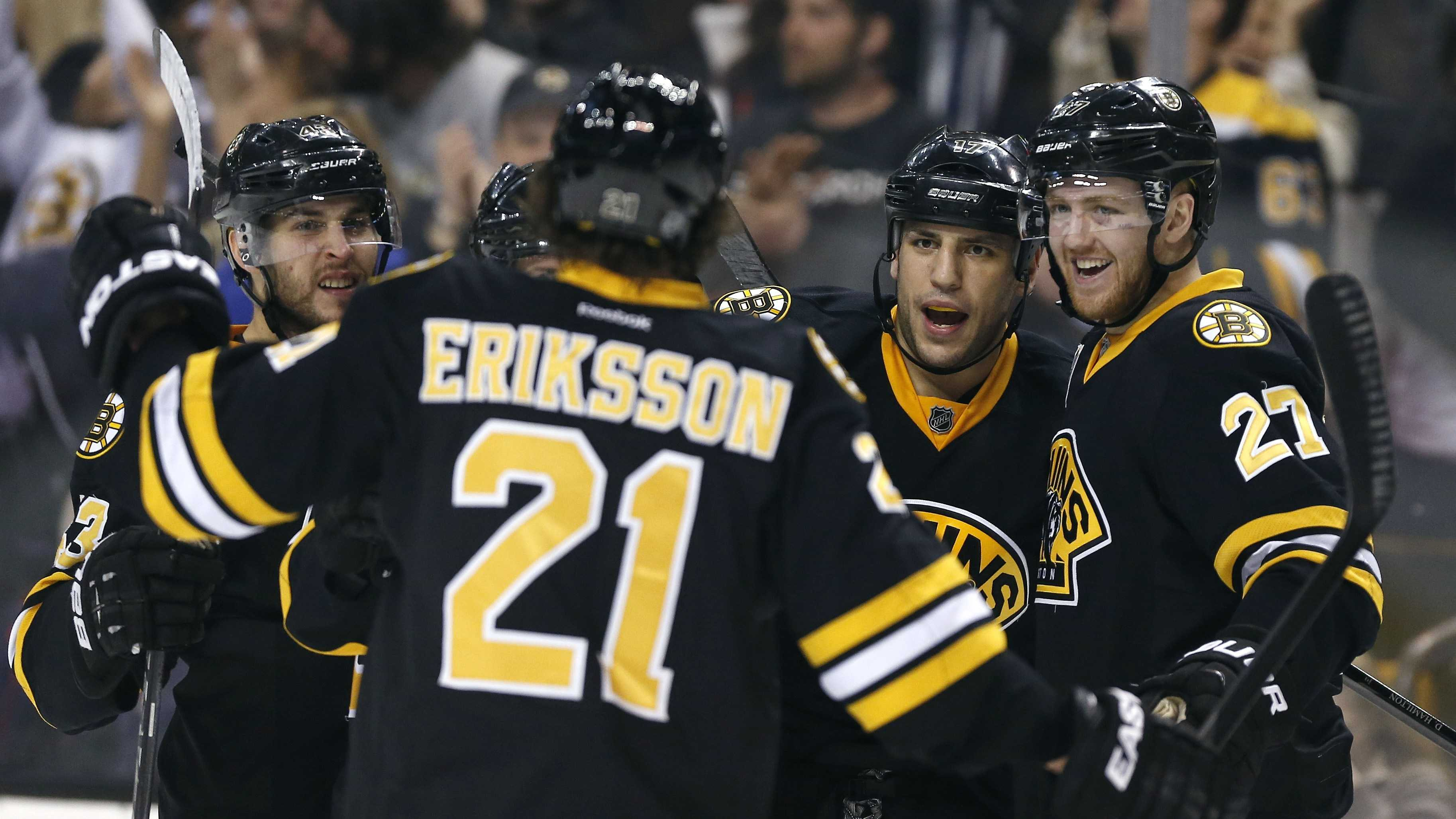 Boston Bruins' Milan Lucic (17) celebrates his goal with teammates Dougie Hamilton (27) and Loui Eriksson (21) in the second period of an NHL hockey game against the Philadelphia Flyers in Boston, Saturday, April 5, 2014. (AP Photo/Michael Dwyer)