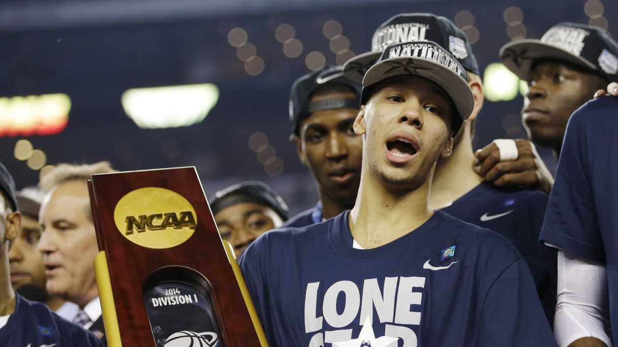 Connecticut guard Shabazz Napier holds the championship trophy after defeating Kentucky 60-54, at the NCAA Final Four tournament college basketball championship game Monday, April 7, 2014, in Arlington, Texas.