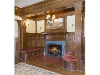 Features include 3 tall stories with turreted dormers, a reception hall with carved wooden walls and fireplaced inglenook, diamond paned windows, ornamental ceilings, and 7 fireplaces.