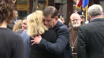 Mayor Marty Walsh hugs a victim's family member as Cardinal O'Malley looks on.