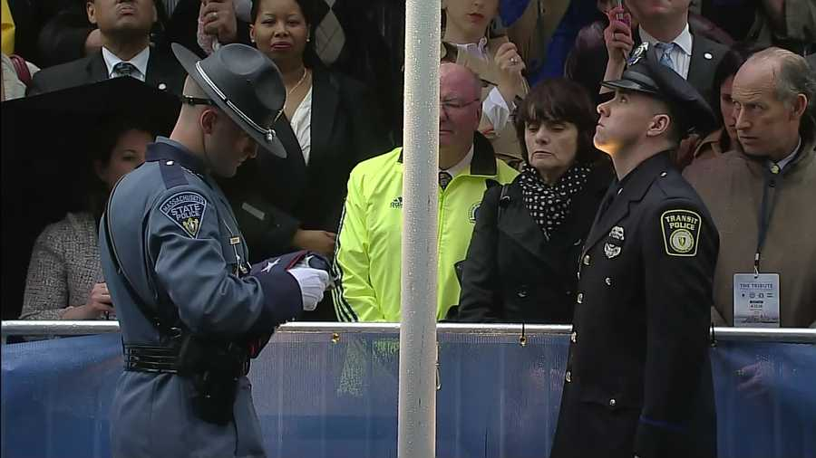 Officer Dic Donohue, who was injured in a shootout with the suspects, raises the American flag.