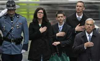 The family of 2013 Boston Marathon bombing victim Martin Richard, from left, mother Denise, brother Henry, and father Bill Richard, place their hands over their hearts as they stand with former Boston Mayor Tom Menino, right, during a tribute in honor of the one year anniversary of the Boston Marathon bombings.