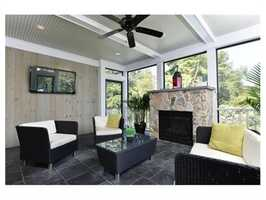 A screened in porch with stone floor and outdoor fireplace for extended seasonal enjoyment