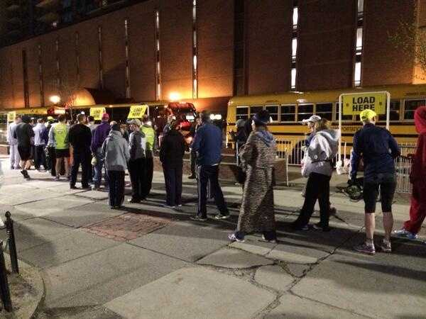 Runners board buses in Boston along Tremont Street to head to the Starting Line.