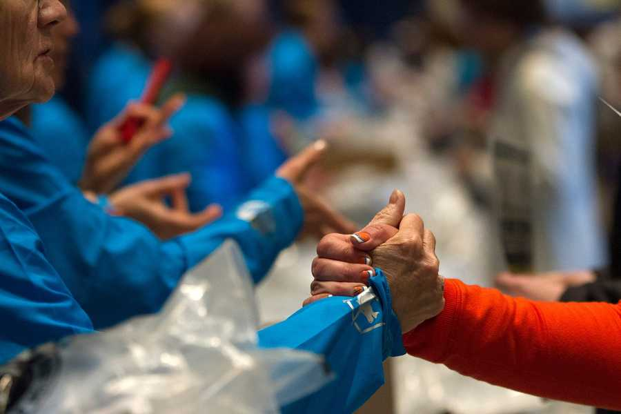 Volunteer Harriet Patoh gives support to runners as they pick up their Marathon t-shirts at the Hynes Convention Center in Boston, Mass.