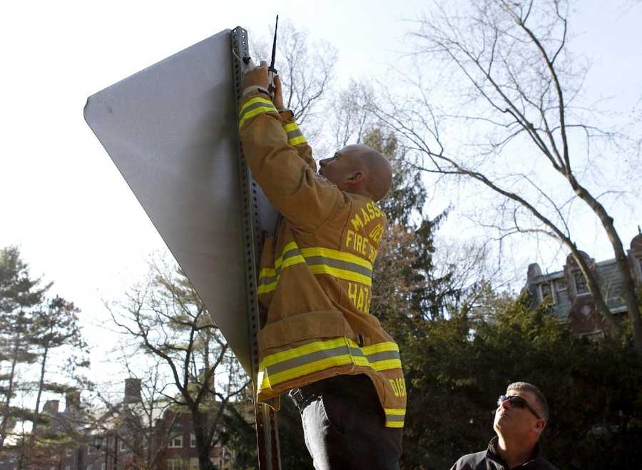 A member of the Massachusetts Department of Fire Services Haz-Mat crew affixes a device to the back of a street sign in front of Wellesley College before the start of the 118th Boston Marathon Monday, April 21, 2014 in Wellesley, Mass.
