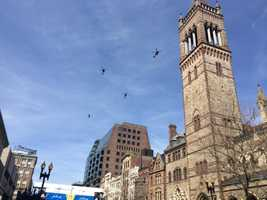 Members of the Massachusetts Army National Guard conduct a flyover at the Boston Marathon start and finish line.