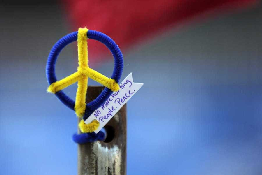 "A peace symbol bearing the words of 2013 Boston Marathon bombing victim Martin, ""No more hurting people. Peace,"" is affixed to a pole near the finish line."