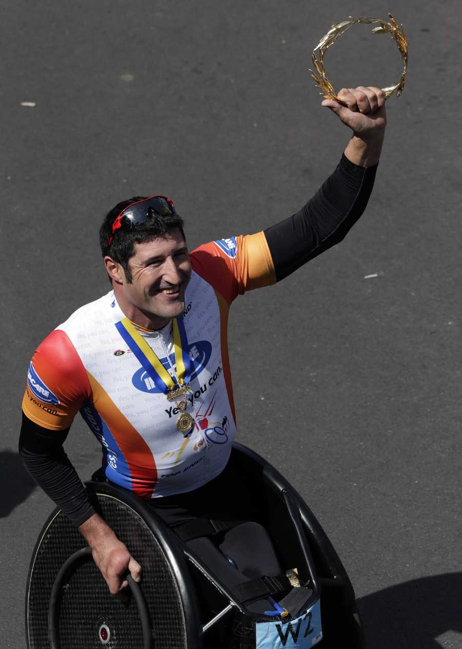 Ernst Van Dyk, of South Africa, hoists his victor's wreath after winning the men's wheelchair division of the 118th Boston Marathon Monday, April 21, 2014 in Boston.