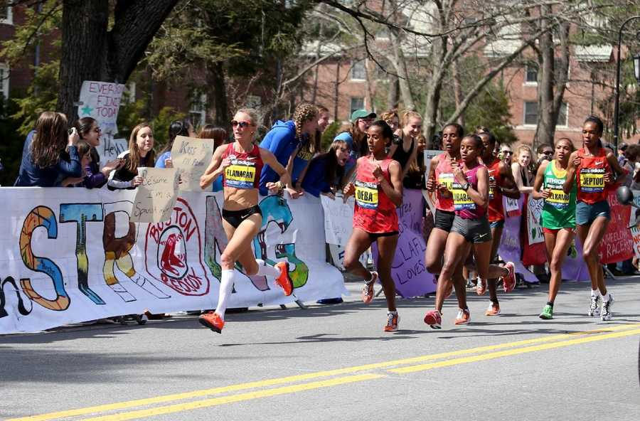Shalane Flanagan leads Buzunesh Deba, of Ethiopia, and Mare Dibaba, of Ethiopia, and the elite pack past the cheering Wellesley College students during the 118th Boston Marathon Monday, April 21, 2014 in Wellesley.