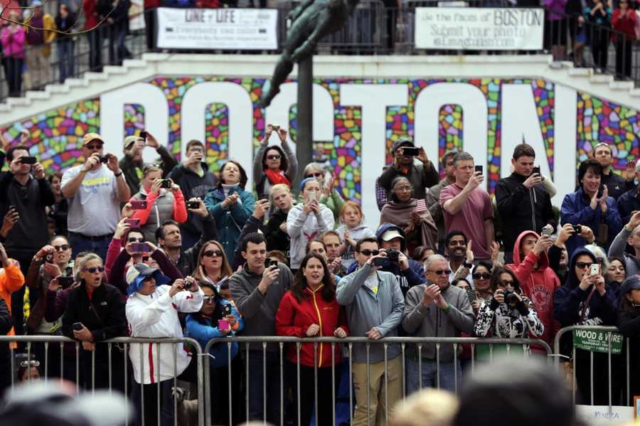 Race fans photograph and cheer for runners competing in the 118th Boston Marathon, Monday, April 21, 2014, in Boston.