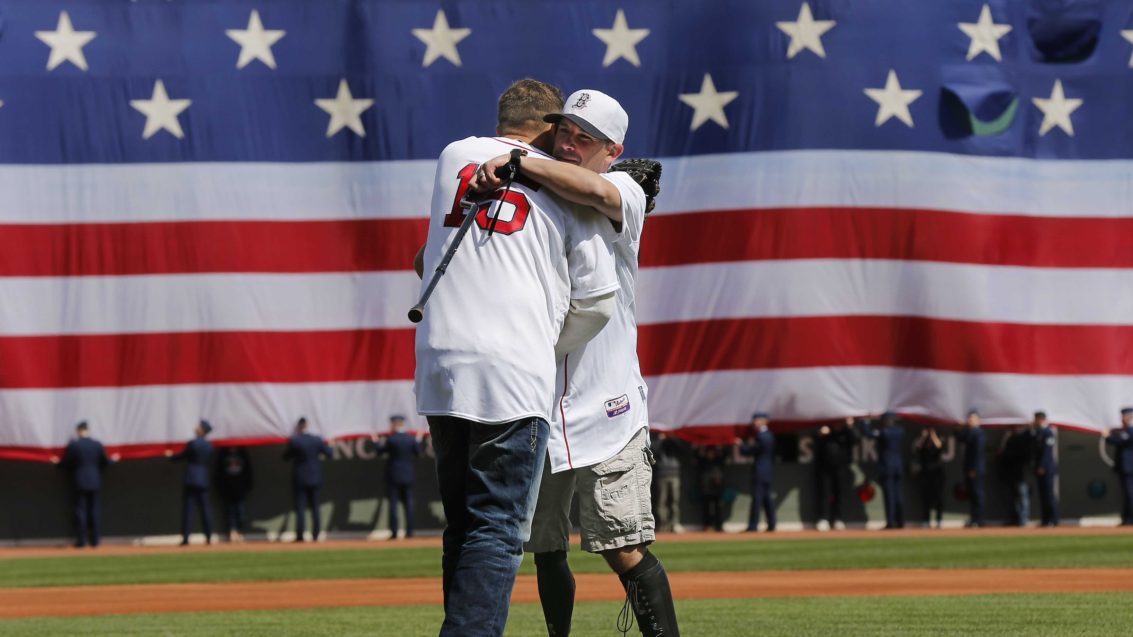 Boston Marathon bombing survivor Marc Fucarile hugs former Red Sox player Kevin Millar after throwing out the ceremonial first pitch before the baseball game between the Boston Red Sox and the Baltimore Orioles at Fenway Park in Boston Monday, April 21, 2014.