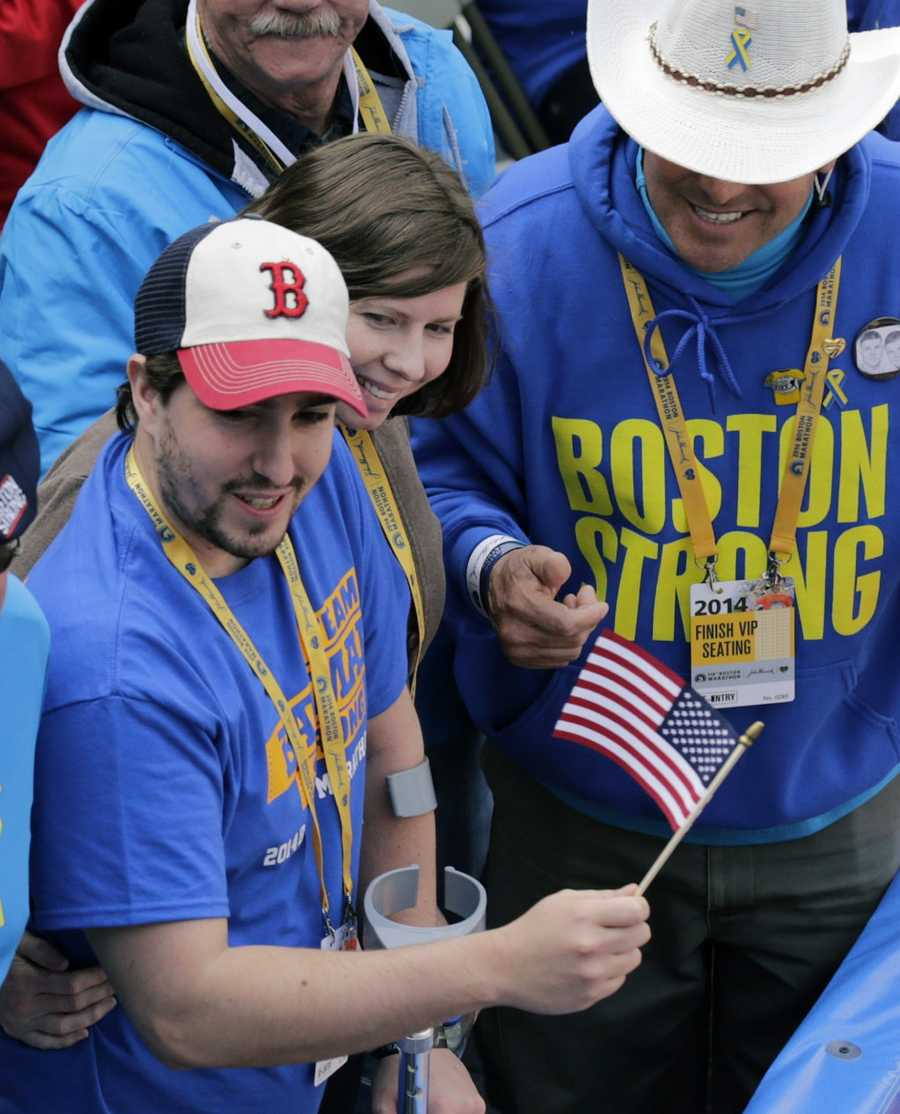 Boston Marathon bombing survivor Jeff Bauman waves an American flag alongside his fiancee Erin Hurley and Carlos Arredondo, right, the cowboy hat-wearing spectator who was hailed as a hero for helping the wounded after the bombings, near the finish line of the 118th Boston Marathon Monday, April 21, 2014 in Boston.