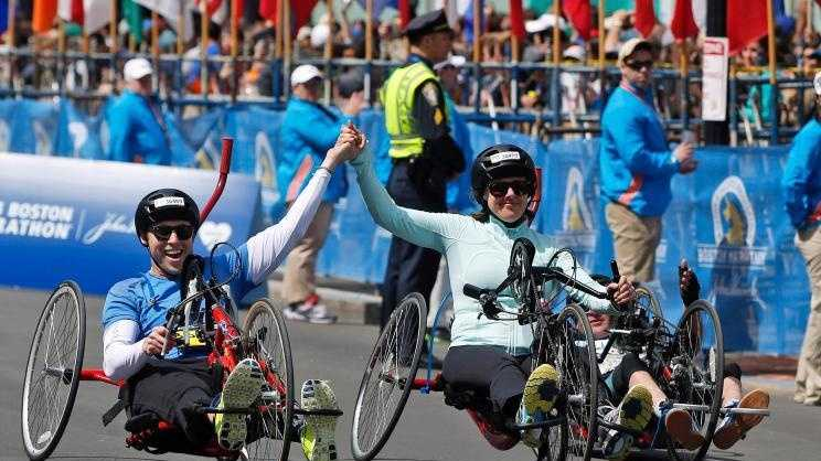 Boston Marathon husband and wife bombing survivors Patrick Downes and Jessica Kensky, who each lost a leg in the Boston Marathon bombings, roll across the finish line in the 118th Boston Marathon Monday, April 21, 2014 in Boston.
