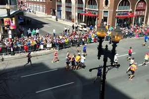 A group of marathon runners on Boylston Street help carry a person to the finish line.