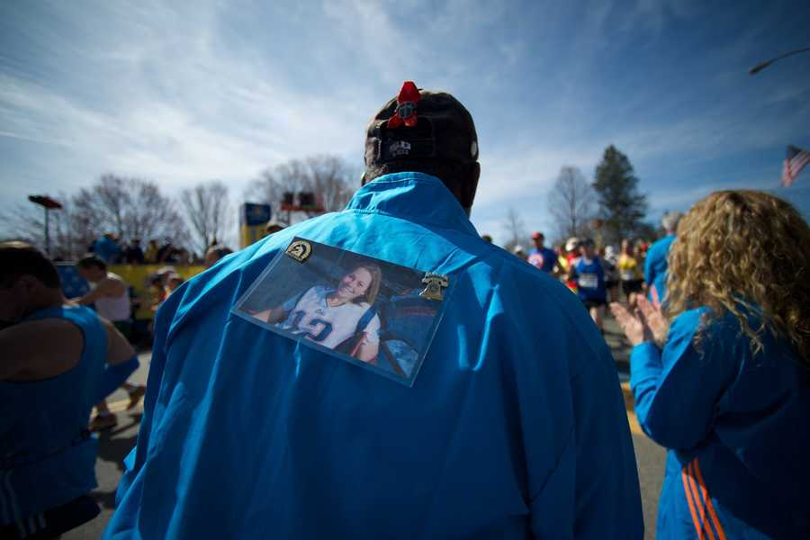 Course volunteer Keith Pearson (far left) wears a picture of Krystle Campbell, who was killed in last year's Boston Marathon bombing at the starting line of the Boston Marathon in Hopkinton, Mass.