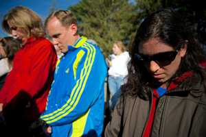 Spectators observe a moment of silence for the victims of last year's Boston Marathon bombing at the starting line of the Boston Marathon in Hopkinton, Mass.