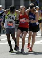 Hugo R. Gonzalez Sr., left, of Miami, and Kyle Brumbaugh, right, of Dayton Ohio, assist Skye Taylor, of Columbus, Ohio, after she collapsed approaching the finish of the 118th Boston Marathon Monday, April 21, 2014 in Boston.