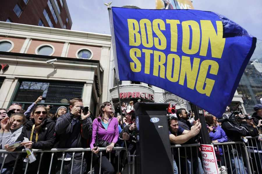 "Race fans with a ""Boston Strong"" flag cheer for competitors near the finish line of the 118th Boston Marathon, Monday, April 21, 2014, in Boston."