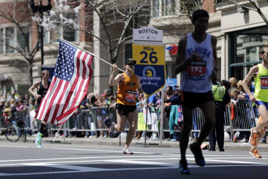 Donny Sazama, of Hermantown, Minn., carries an American flag as he runs past the 26 mile mark of the 118th Boston Marathon Monday, April 21, 2014 in Boston.