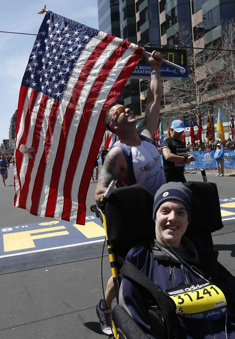 Lucas Carr, rear, celebrates after pushing Matt Brown across the finish line in the wheelchair division of the 118th Boston Marathon Monday, April 21, 2014 in Boston.