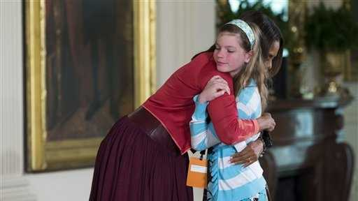 "First lady Michelle Obama hugs Charlotte Bell, 10, after she handed Mrs. Obama her dad's resume during the White House's annual ""Take Our Daughters and Sons to Work Day."" The girl told the first lady that her dad had been out of work for three years. Then the girl popped up to hand Mrs. Obama her dad's resume saying ""My dad's been out of a job for three years and I wanted to give you his resume."""