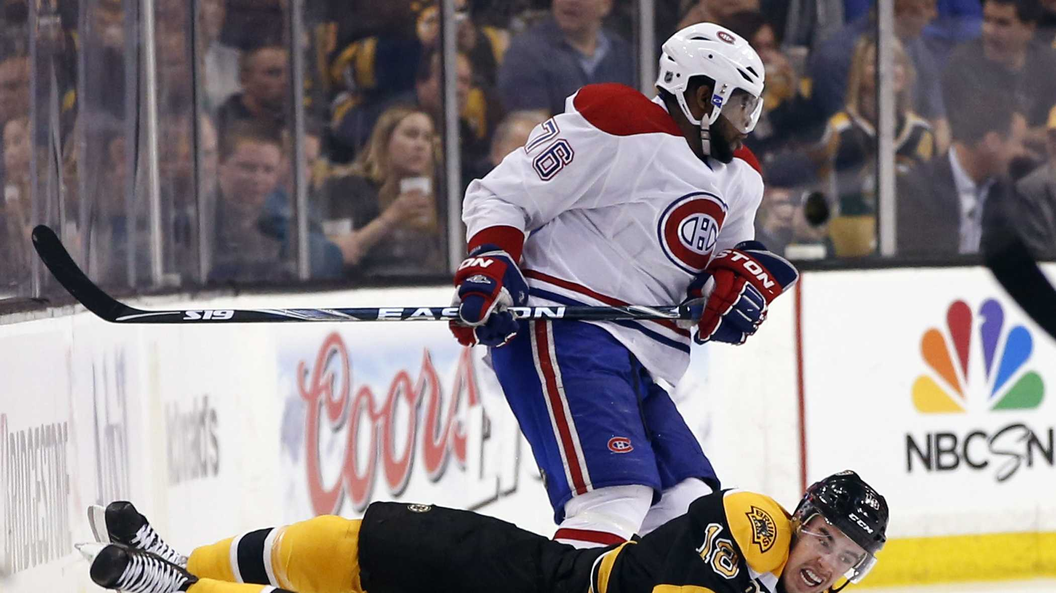 Boston Bruins right wing Reilly Smith (18) falls to the ice after crashing with Montreal Canadiens defenseman P.K. Subban (76) during the first period in Game 1 of an NHL hockey second-round playoff series in Boston, Thursday, May 1, 2014.