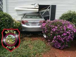 A woman was taken to Newton-Wellesley Hospital Saturday afternoon after crashing her car into the front of her own home, according to a Natick fire official.