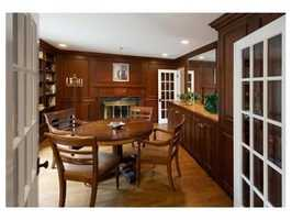 Paneled library with fireplace and wetbar