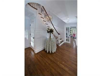 Large welcoming foyer with detailed woodwork and curved staircase.