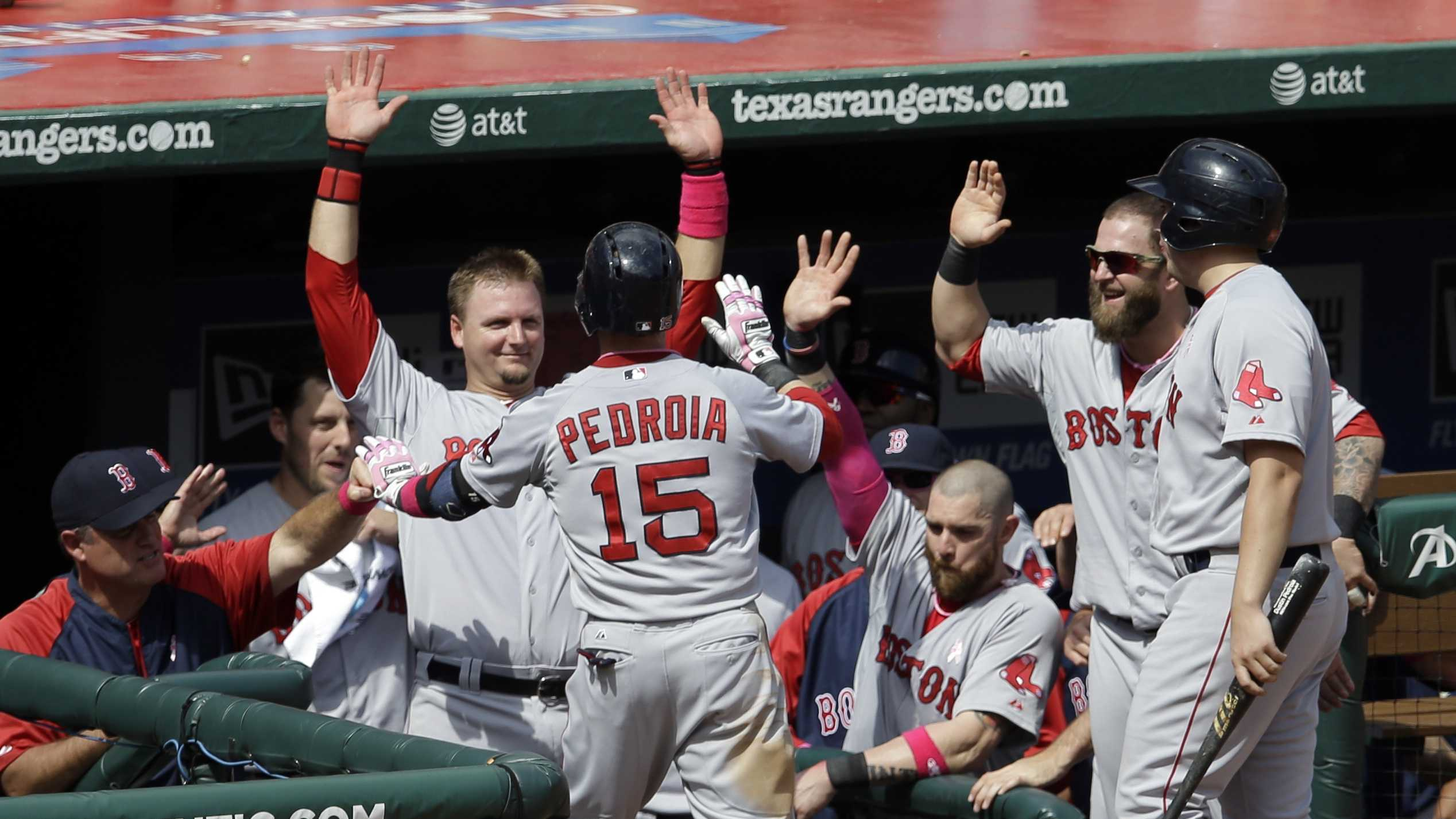 Boston Red Sox's Dustin Pedroia (15) is congratulated at the top of the dugout by manager John Farrell, left,catcher A.J. Pierzynski and Mike Napoli, second from right, following his solo home run off Texas Rangers' Robbie Ross in the seventh inning of a baseball game on Sunday, May 11, 2014, in Arlington, Texas. (AP Photo/Tony Gutierrez)